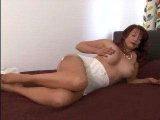На кровати женщина в чулках ласкает себя